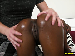 Dark skinned babe Malaysia Slick gets oiled before riding white dick